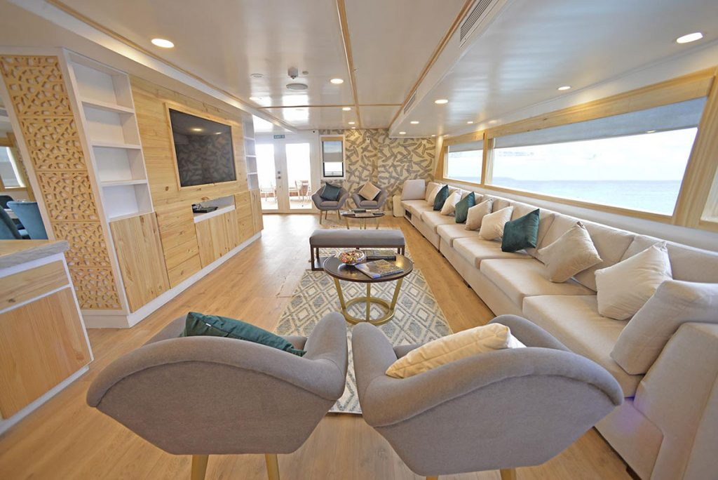 The Sea Star cruise's lounge has light wood floors, modern gray cushioned chairs, a long white sofa below an equally long window, and small circular coffee tables. A TV is mounted seamlessly into the light wood wall.