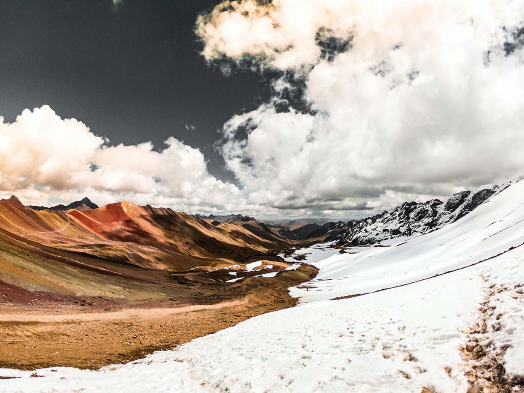 Snow mountains to the right and the Rainbow Mountain to the left, with a cloudy sky