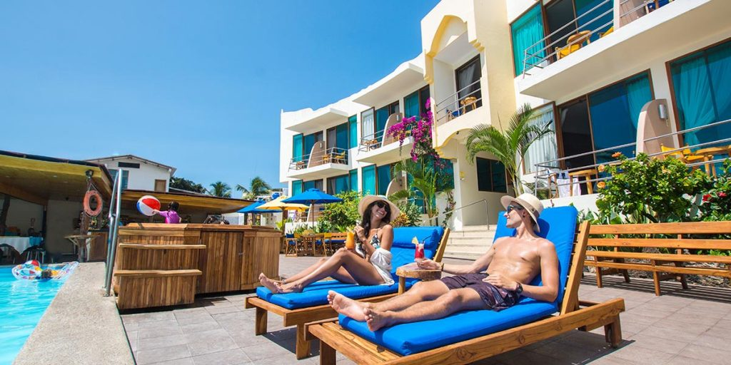 A couple sits on bright blue cushioned lounge chairs next to a pool with balconies of the hotel Solymar behind them.