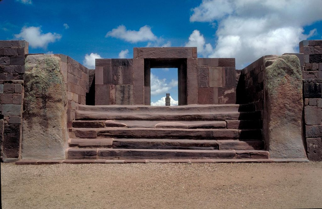 A small statue stands framed by the stone ruins of Tiwanaku in Bolivia.