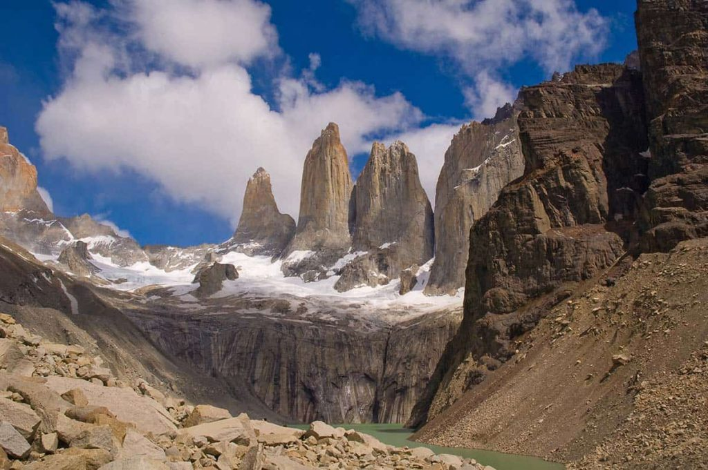 The Torres del Paine mountains reach high into the sky. A bit of snow can be seen in the image.