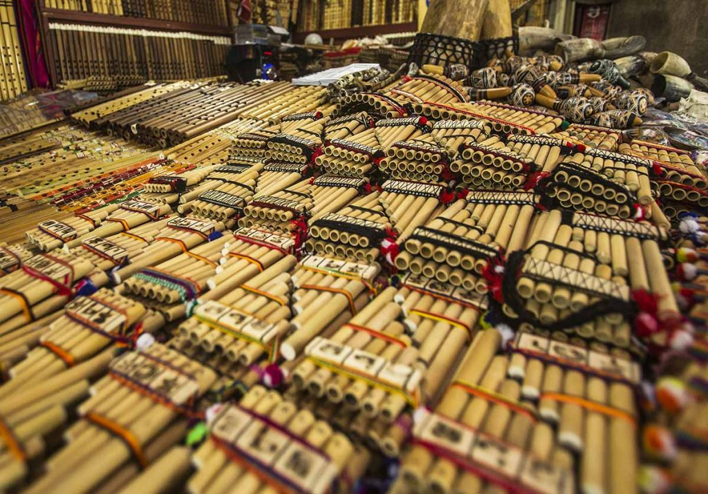 Many Andean panflutes sit in rows and stacks at a Peruvian market surrounded by flutes, maracas, and drums.