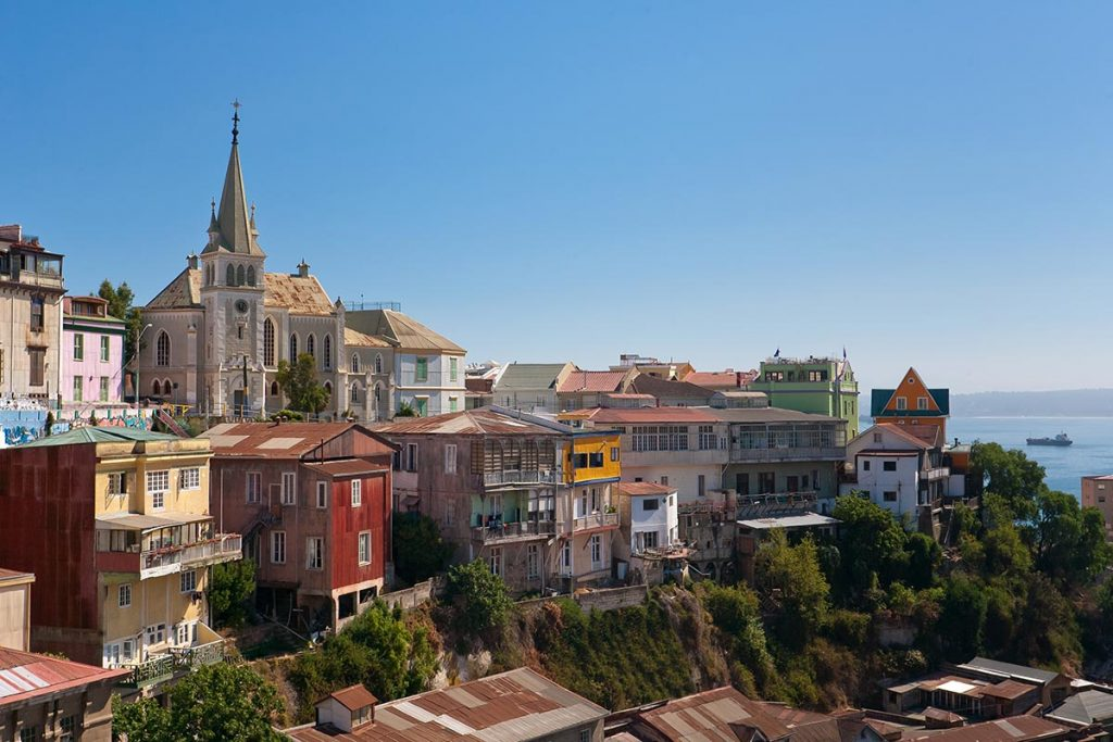 A view of the colorful houses and buildings on the mountainside of Valparaiso in Chile. The ocean can be seen in the distance.