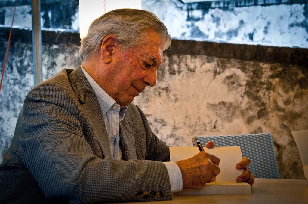 Contemporary Peruvian author Mario Vargas Llosa signs a copy of one of his books.