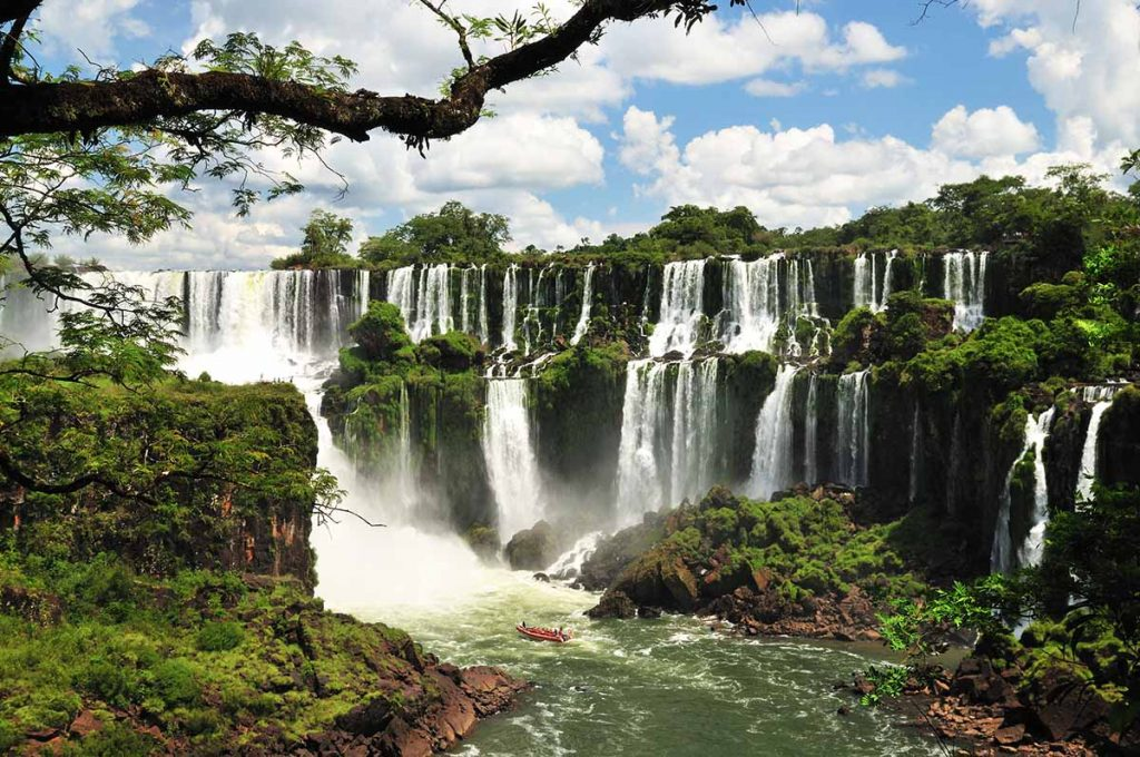 A small boat floats in the pool of water formed by the massive Iguazu Falls. Many streams of water cascade downward on a sunny day.