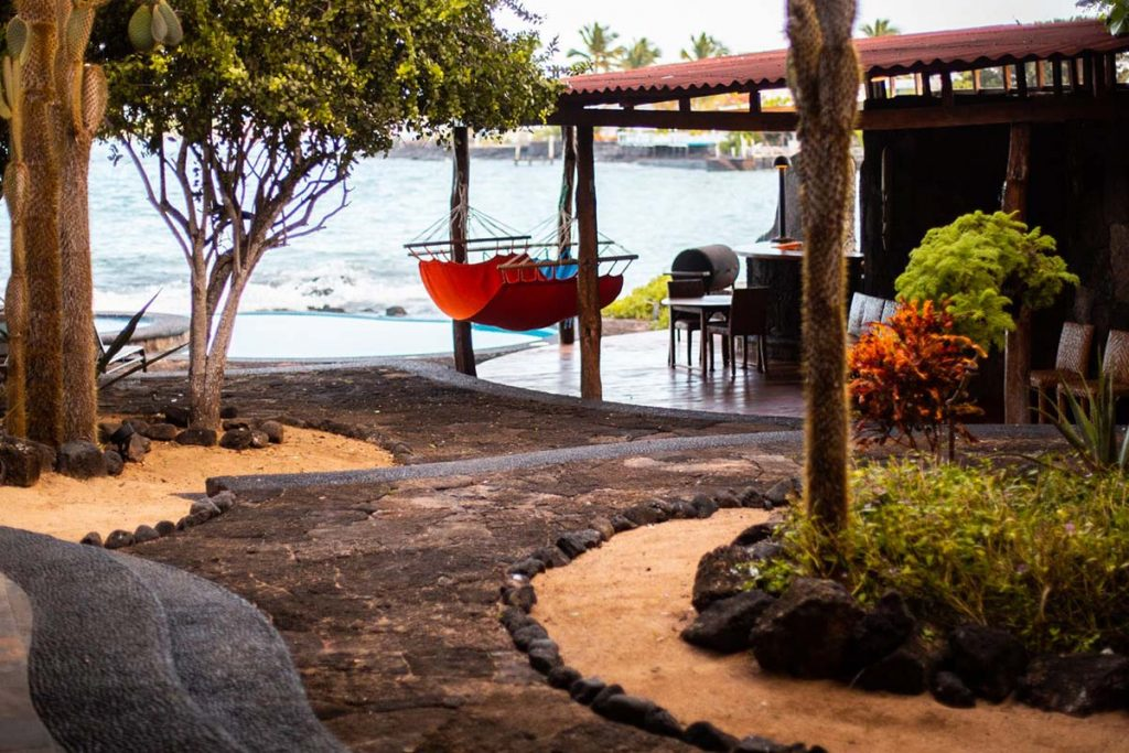 A cobbled walkway curves towards a barbecue area and hammocks before reaching an infinity pool in front of the Santa Cruz harbor.