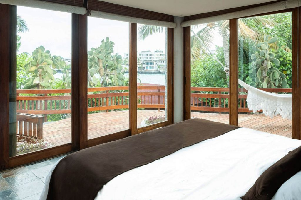 A king sized bed with white linens and dark brown accents faces dark wood-lined floor to ceiling windows and a large private deck. Pelican Bay is seen in the background.