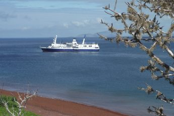 A Galapagos cruise sits off the shores of a red sandy beach.