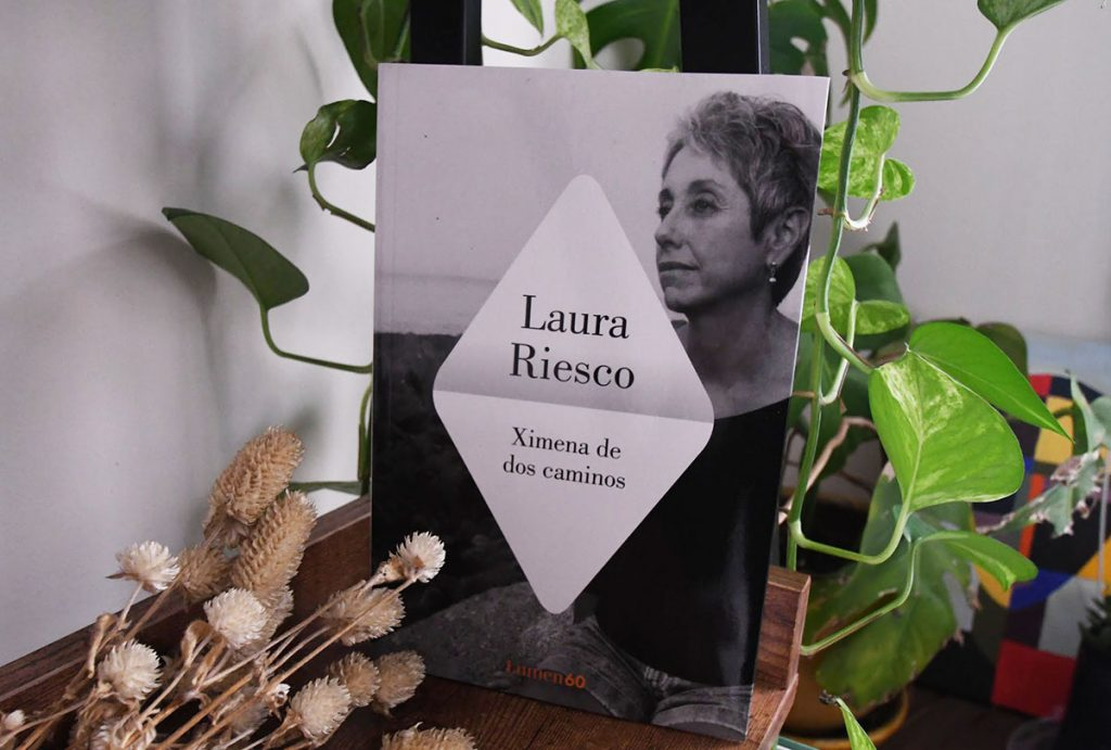 """The book """"Ximena at the Crossroads"""" by Laura Riesco, with black and white cover art featuring a photo of the author sits alone on a bookshelf surrounded by hanging plants and dried flowers."""