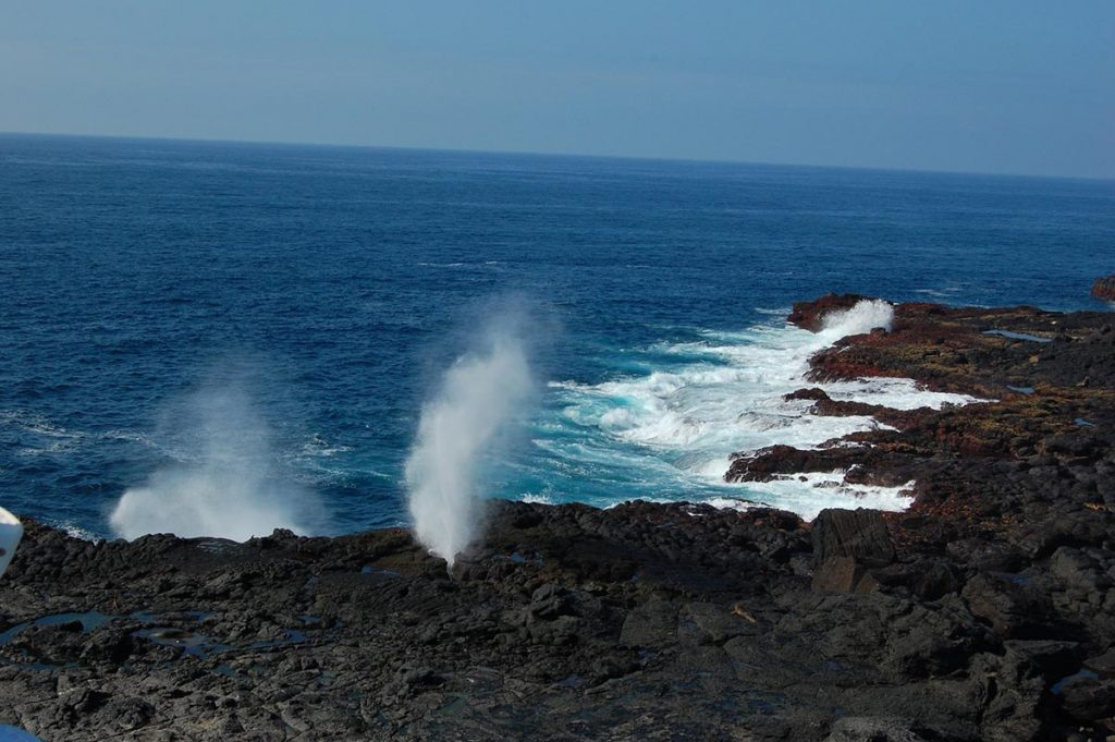 A geyser like wave breaks on jagged black lava rock on a sunny, cloudless day.