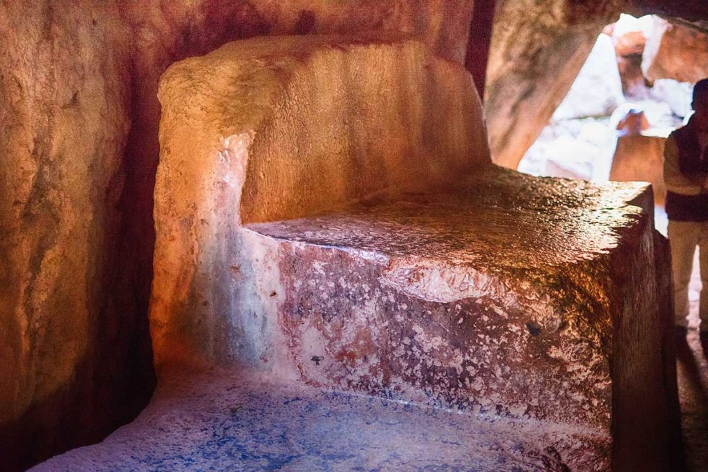 A smoothly cut stone slab with a raised back inside of a stone tunnel at the Qenqo archeological site. A tourist stands out of focus in the background towards the tunnel's opening.
