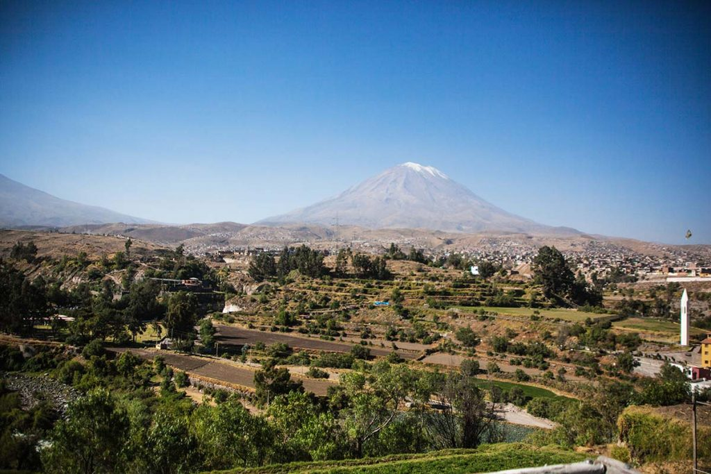 Arequipa's Mistvi Volcano rising behind a countryside landscape.