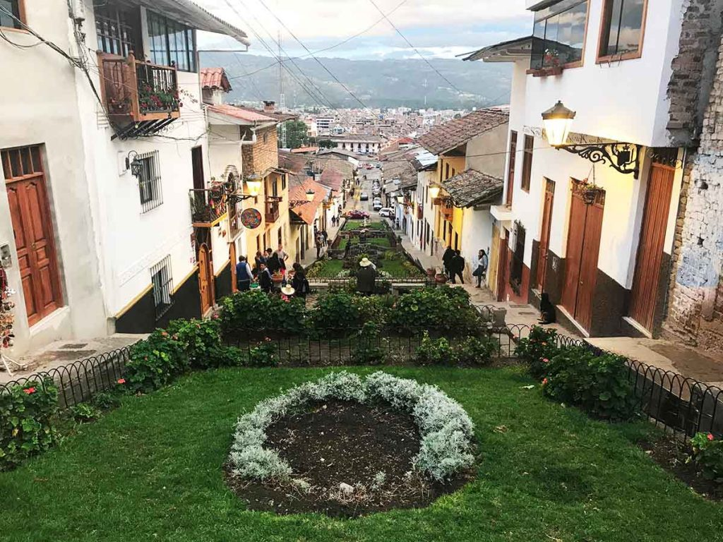 View from atop of a sloping Cajamarca pedestrian street with buildings lining both sides.
