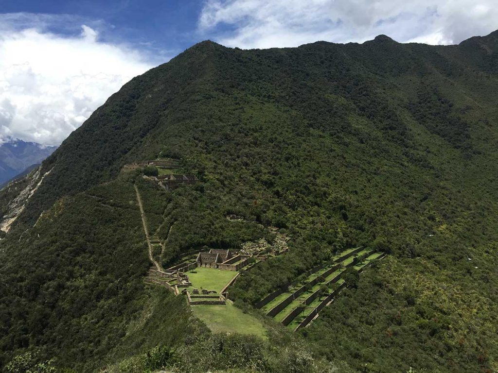 The Choquequirao ruins from above with surrounding forest and blue sky.