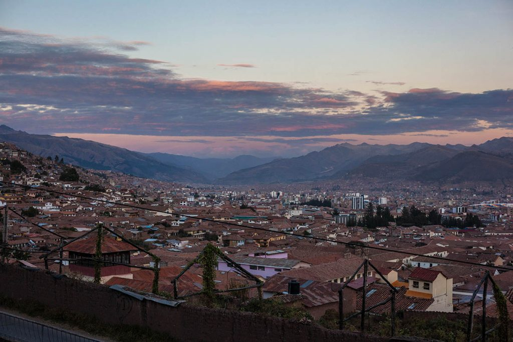 A muted sunset behind an aerial view of Cusco city.