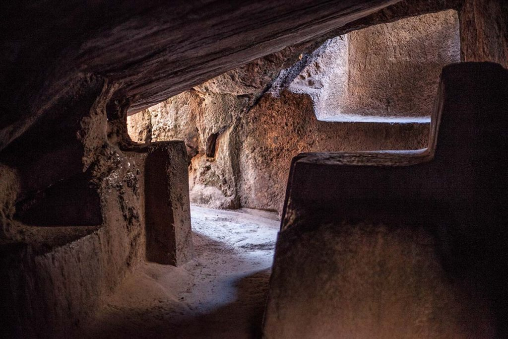 Inside Qenqo's underground tunnel. The sacrificial slab, the low roof, and a distant bank are all smoothly cut from the natural rock.