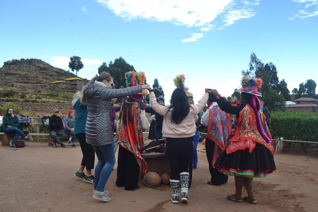 Locals in traditional dress and tourists dance in a circle with their hands joined and raised. Other tourists watch seated in the background.