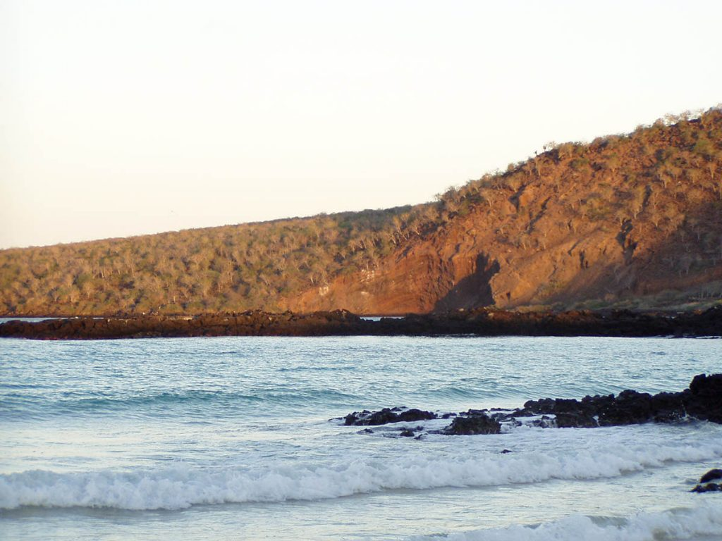 The sun's last rays hit the brownish red hill surrounding a small cove where black lava rocks cut through the waves.