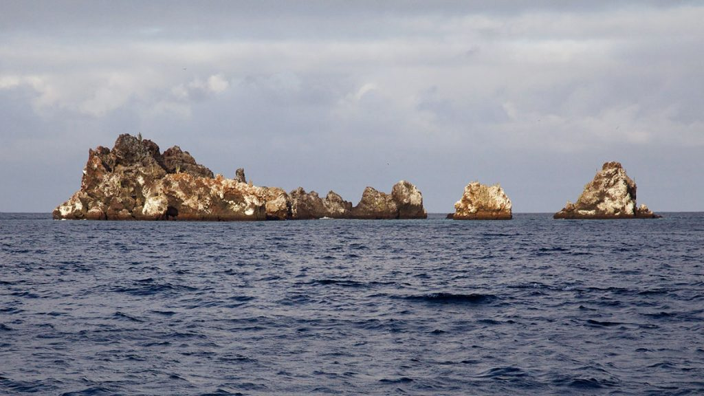 Jagged brown and cream colored rocks jut out of the ocean in a shape vaguely resembling a crown.
