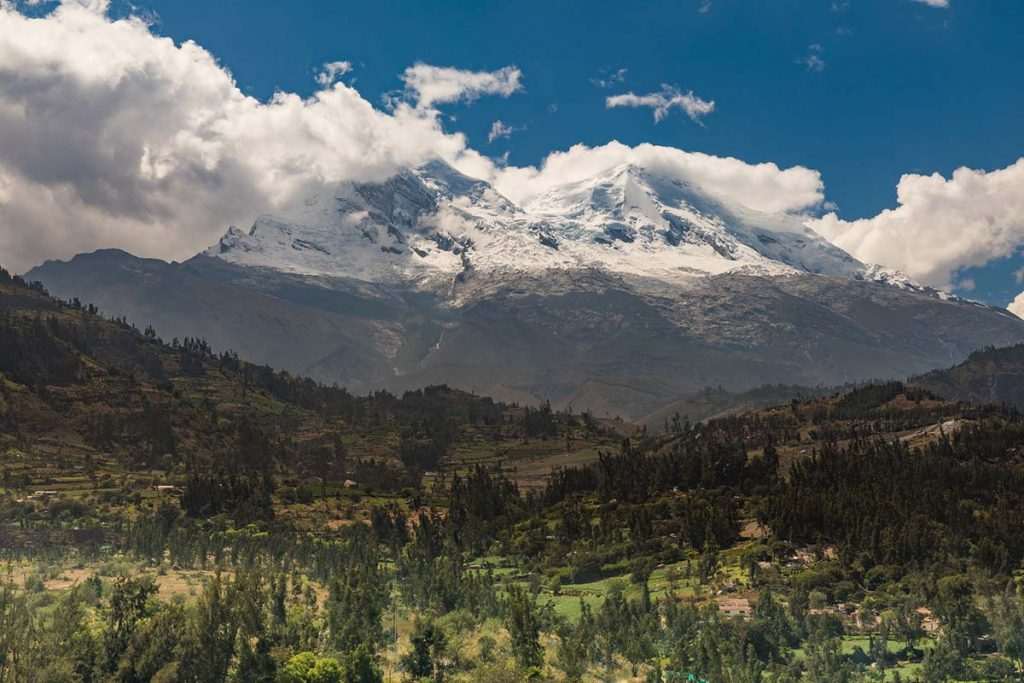 The snow-capped Huascarán Mountain with green evergreen-spotted valley below and blue sky above.