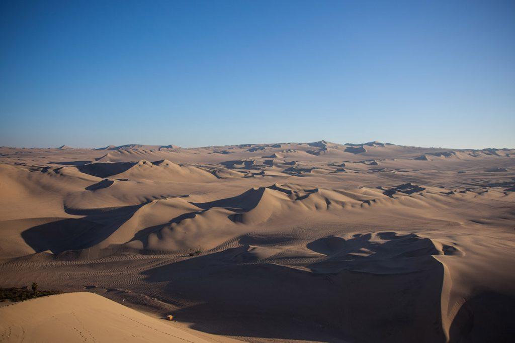 Ica's orange sandy dune landscape with deep blue sky.