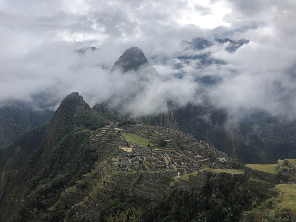 Machu Picchu ruins with mist partially covering the Huayna Picchu mountain.