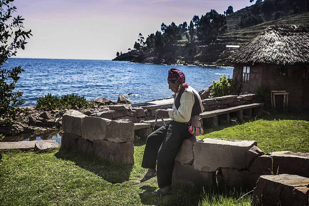 A local Taquile man sits on a low stone wall and knits in front of his thatched roof house with Lake Titicaca behind him.
