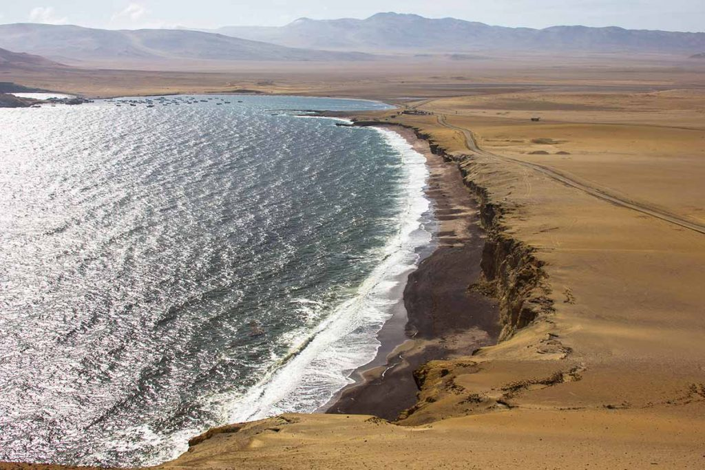 The red sand coast of the Paracas National Reserve and Pacific Ocean.