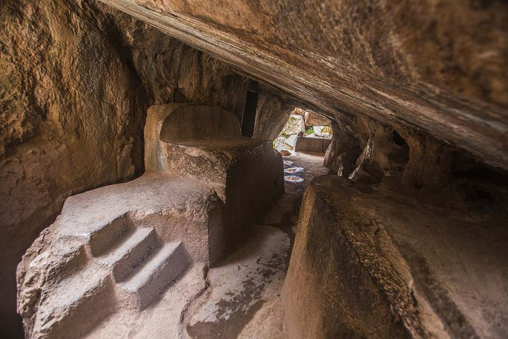 Three steps cut into the natural stone lead up to a smooth slab with a raised back used for ritual sacrifices. The low ceiling is also cut smooth. At the far end of the tunnel is an opening to the outside.