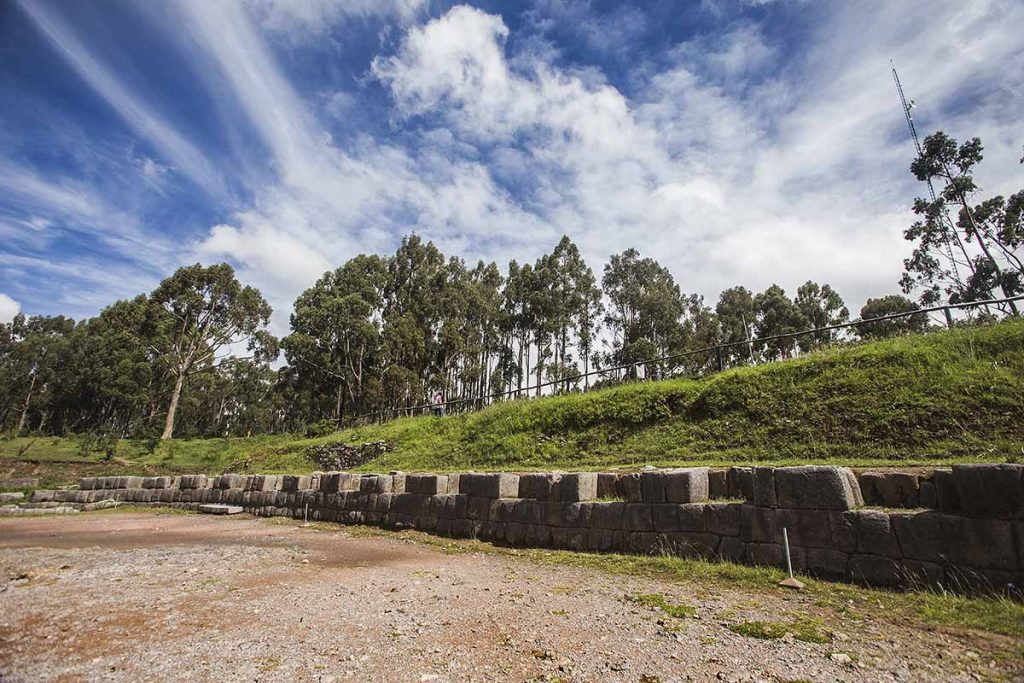 A low wall made of stone bricks lines the edge of Qenqo's amphitheater. There are evenly spaced niches in the stone wall. A low grassy hill and trees lay behind the wall.