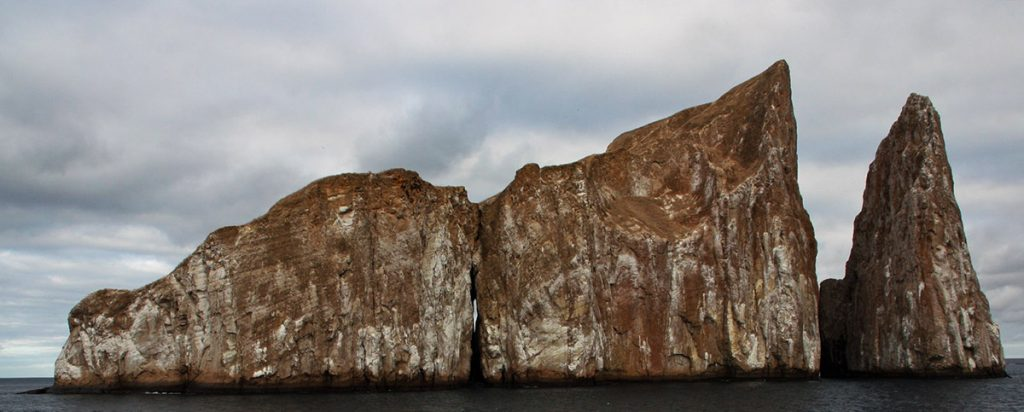A rock that increases in height from left to right, comes out of the ocean with a pointed vertical rock to its right.