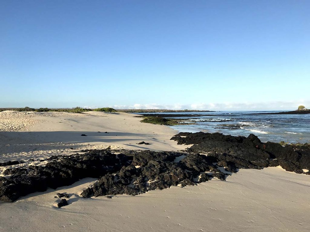 A light beige beach at low tide is divided in two by black lava rock. The sky above is light blue and cloudless.