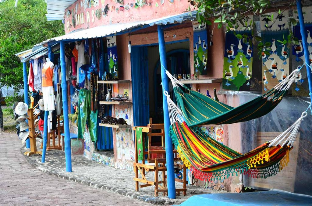 Two souvenir shops selling hammocks, blue footed booby wall hangings and T-shirts sit at the edge of a cobbled street.