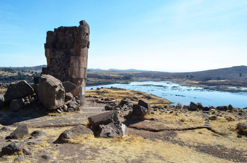 A Sillustani stone chullpa with the blue Lake Umayo in the background.