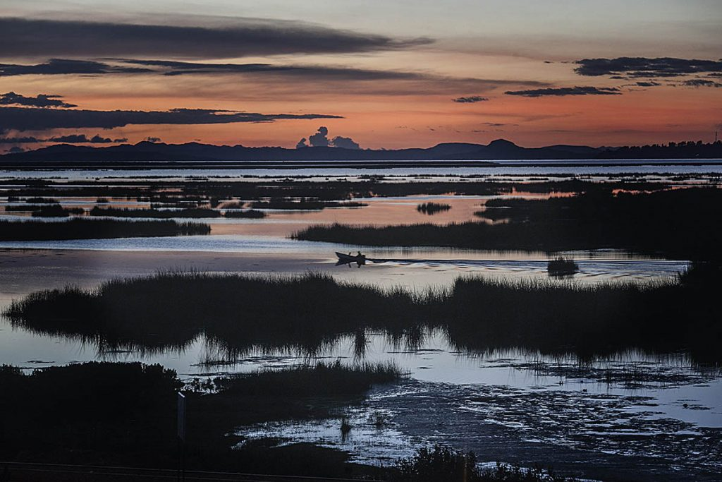 The end of a sunset over the grassy marshes of Lake Titicaca. A small boat passes through the marshes under a muted peach and purple sky with mountains in the distance.