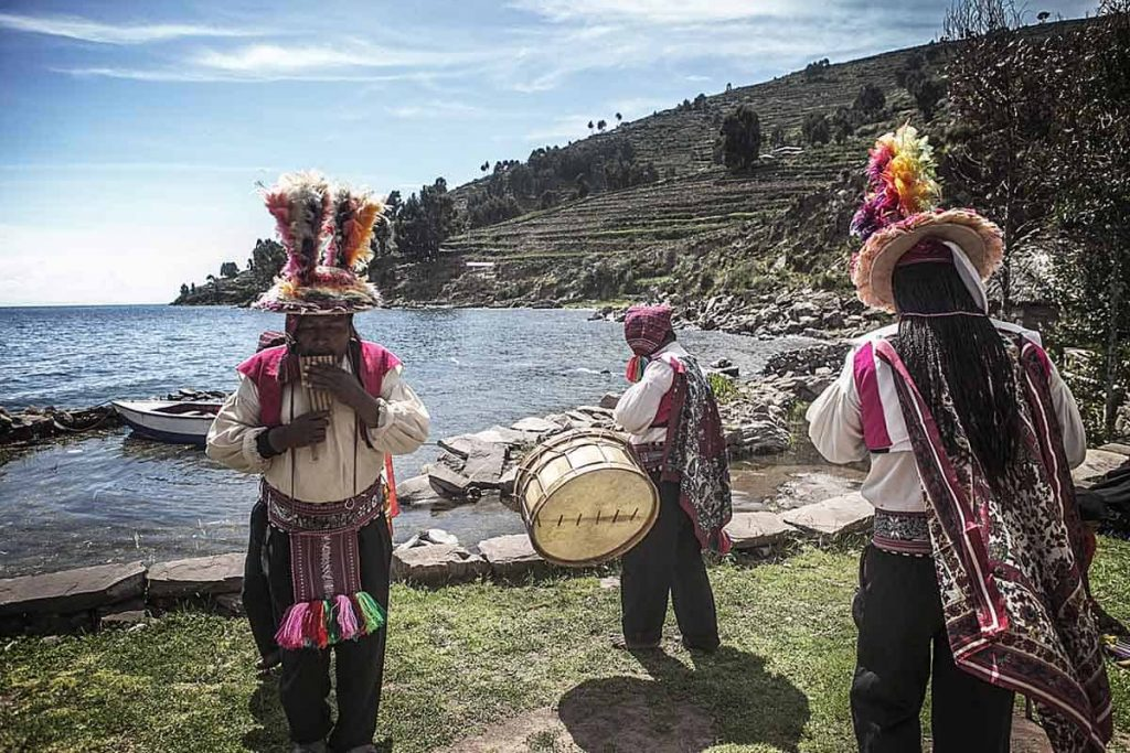 Three Taquile men in traditional dress—black pants, white shirt, woven belt and cape, and feathered hats—play pan flutes and a drum in a circle with the island as a backdrop.