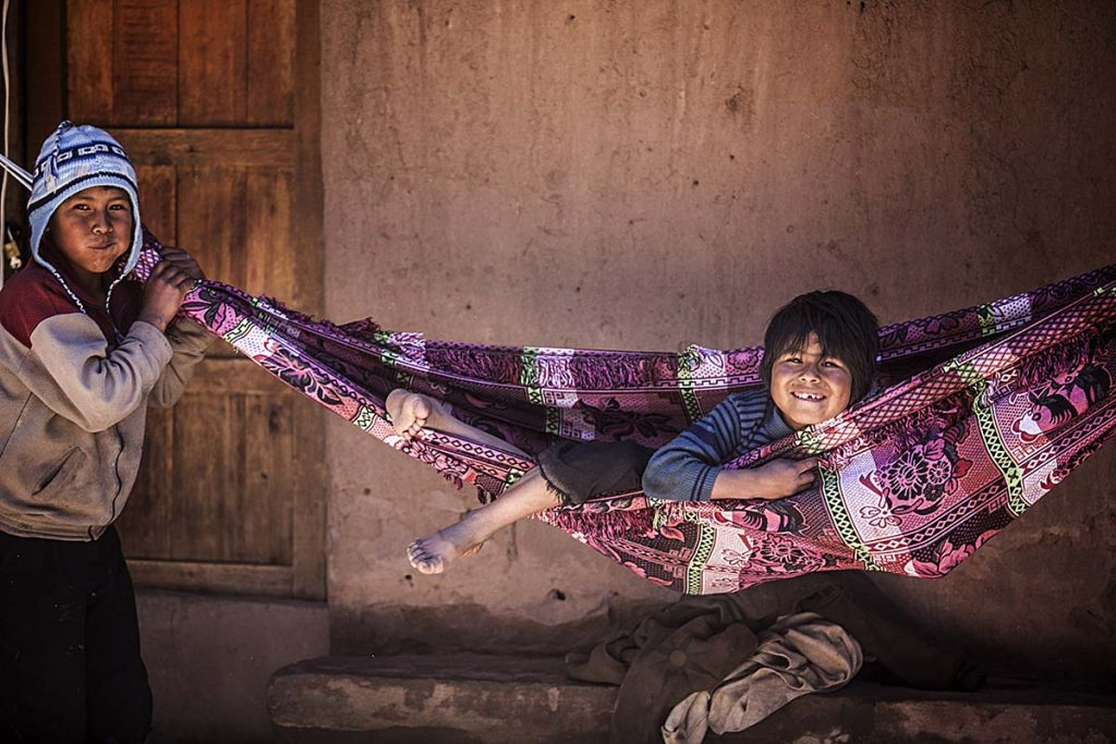 A local Taquile child smiles from a traditional woven hammock with purple flower designs while another child makes a silly face will holding the end of the hammock.