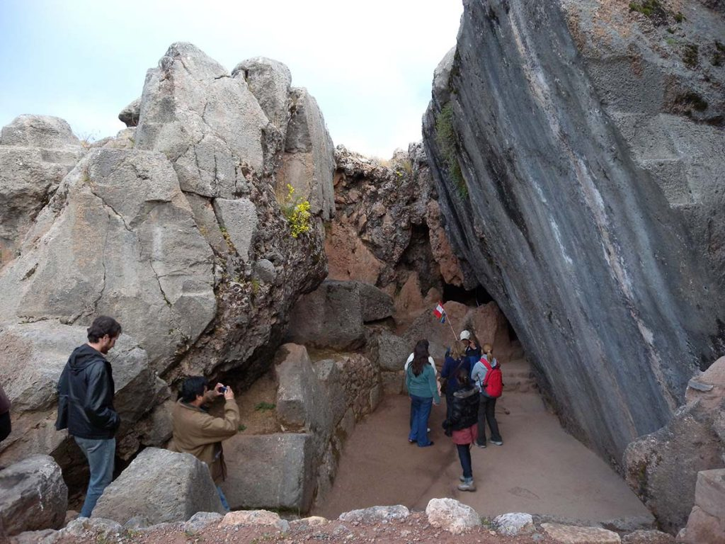 Tourists and their guide gather beneath two large, inwardly inclined stones. The stone on the right is uneven while the stone on the left is smooth.