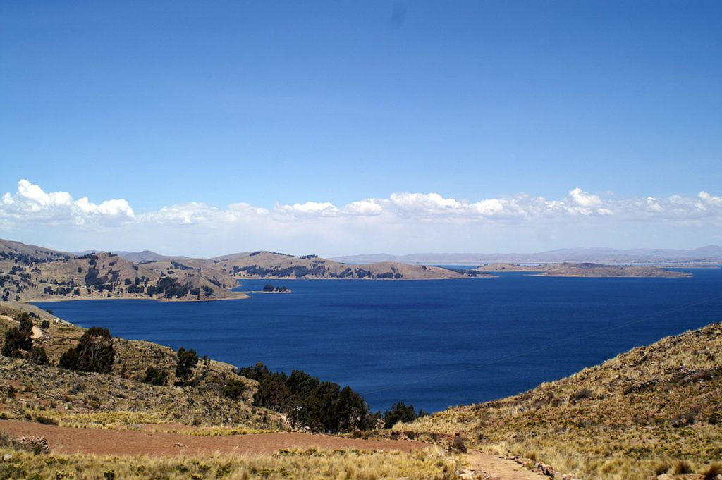 View from the sparsely treed hills of Taquile over the calm waters of Lake Titicaca and surrounding islands on a sunny day.