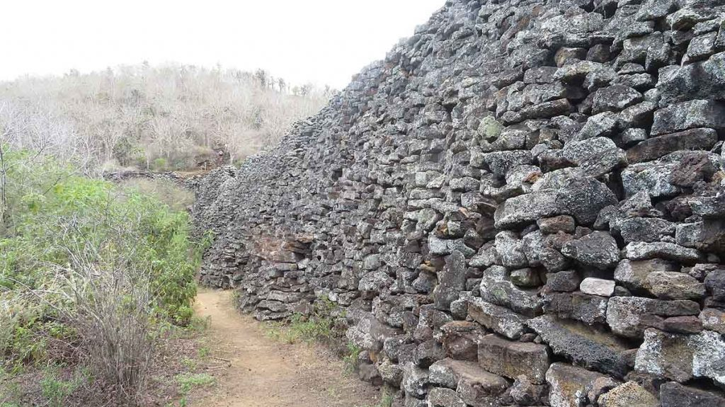 A wall made of large volcanic stones to the right with a dirt path, trees, and bushes to its left.