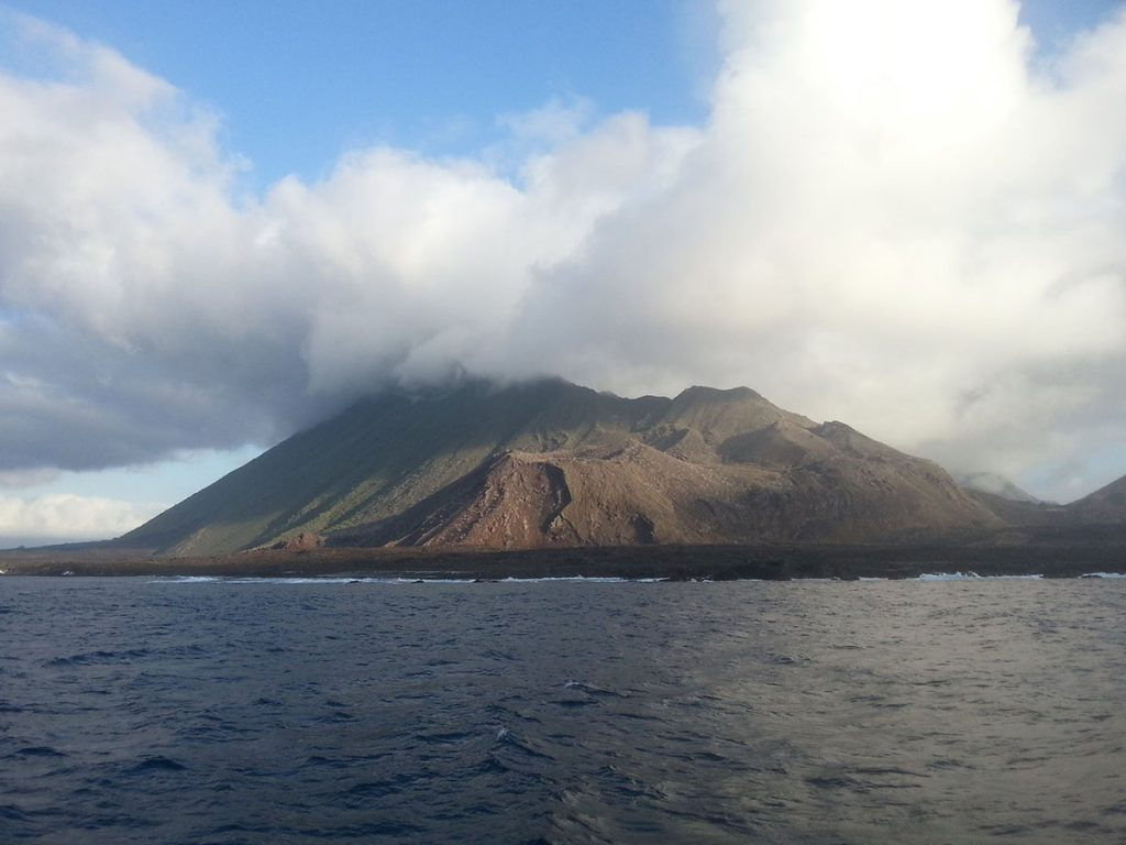 Over a short stretch of ocean, a volcano stands with its point covered by low hanging, fluffy white clouds.