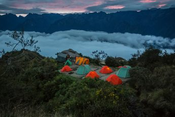 Green and red tents are pitched on a rock clearing surrounded on one side by trees and the other by clouds.