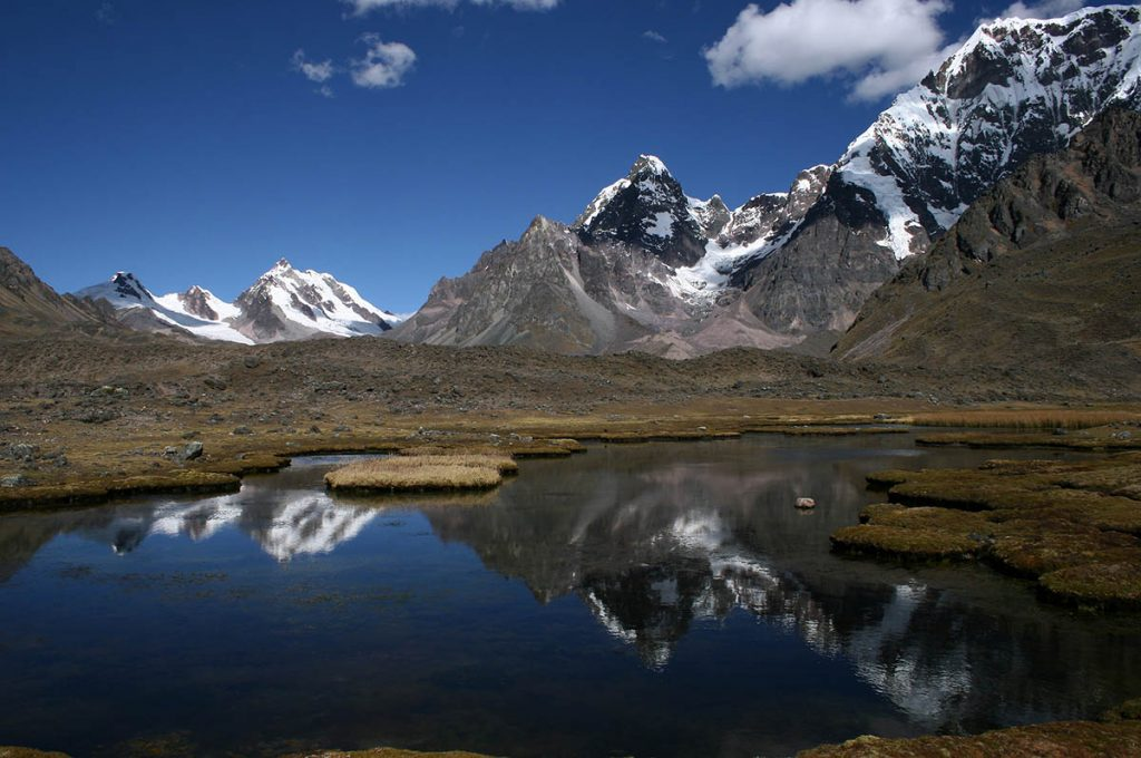 Snow-covered mountains are reflected in a lake on sunny day on the Ausangate trek.