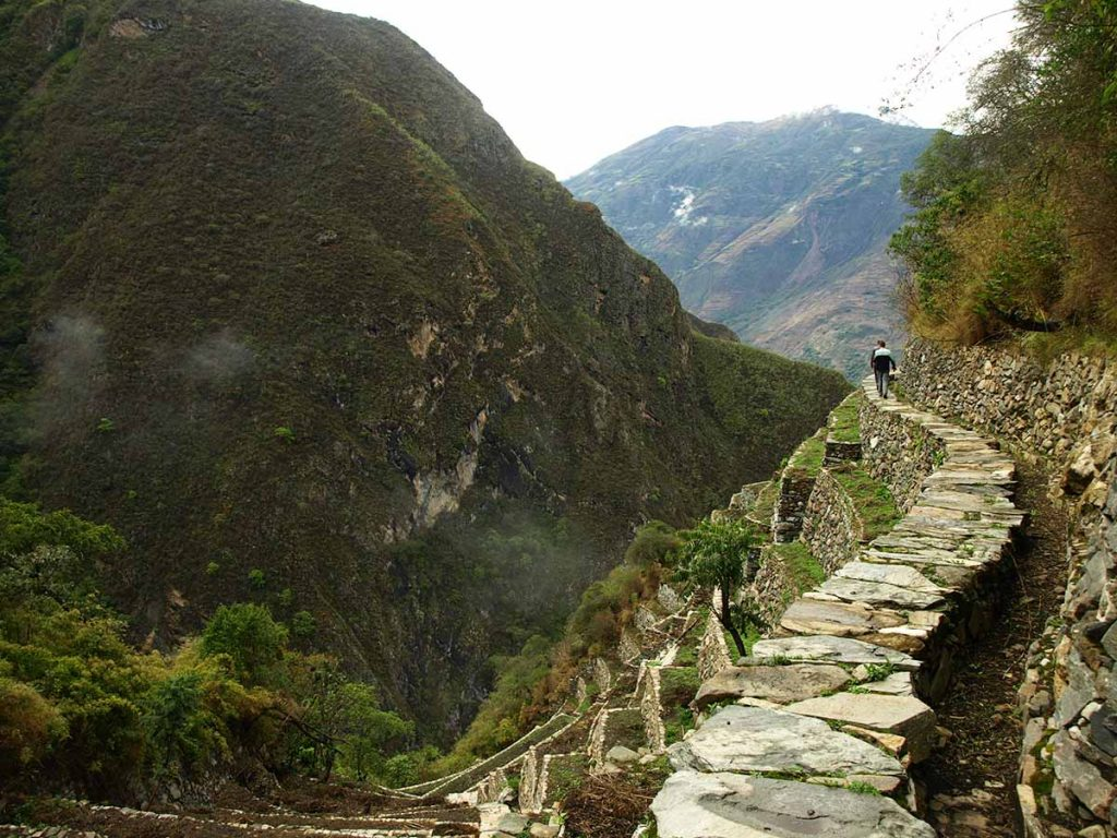 Two people walk along a stone path above Inca terraces surrounded by green mountains.