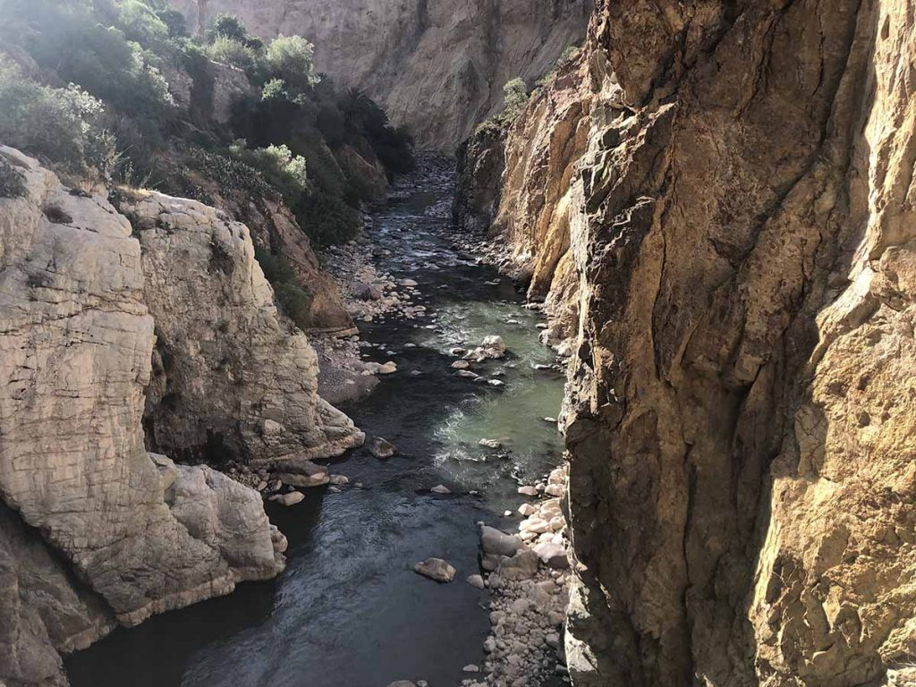 The Colca River flows between two tall rock faces.