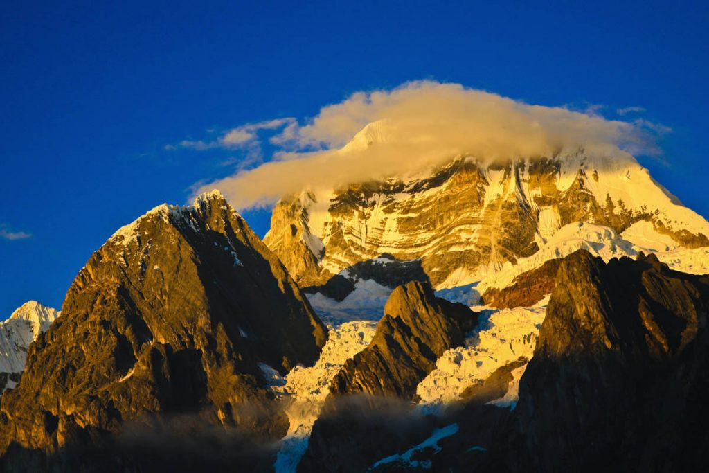 A wispy cloud passes in front of a snow-capped peak at sunset.