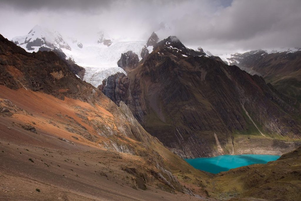 Bare-faced and snow-capped mountains surround a neon blue lake on a cloudy day.