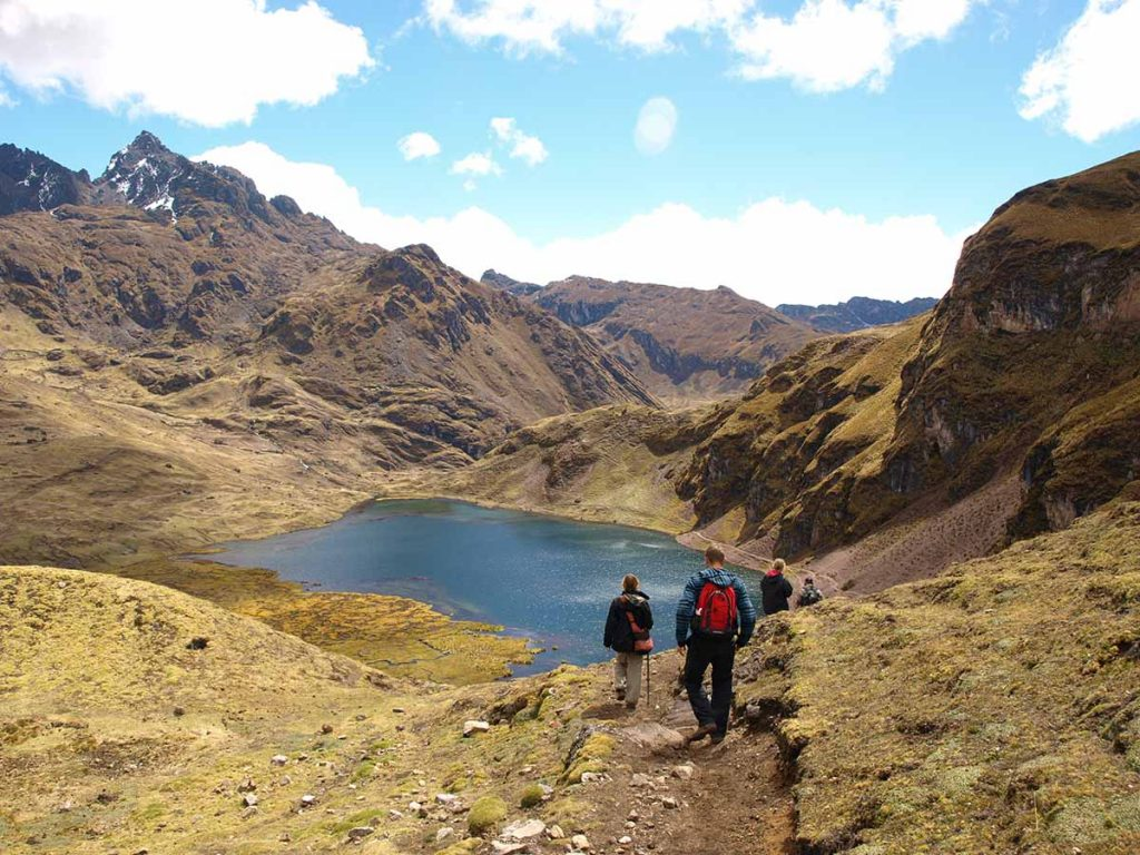 Hikers follow a path down towards a small lake surrounded by craggy mountains.