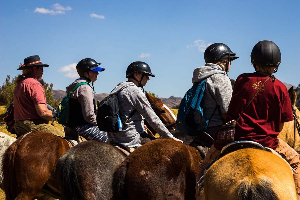 Five people sit in a line on horseback.