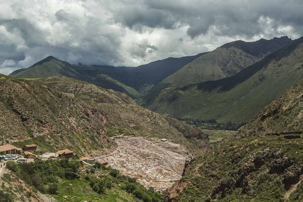 The Salineras de Maras sit on the side of a hill surrounded by green mountains.